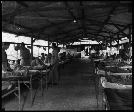 Interior view of typical medical ward. There is a utility building in background with another medical ward beyond