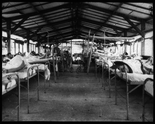 Interior view of typical orthopedic surgical ward, a row of beds occupied by people.