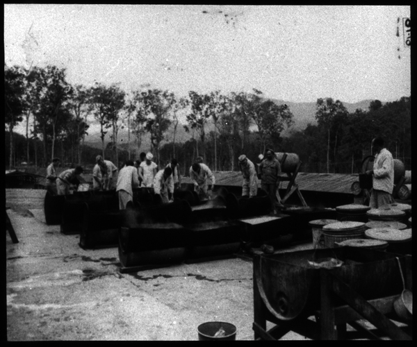 General view from office end of the Medical Supply Building. Note concrete platform and method of heating water in drums for washing mess kits and partitioned mess trays.