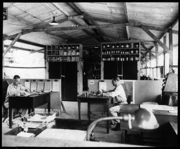 General view from office end of the Medical Supply Building. Typical office furniture including filing cabinets and clipboards, with two men seated at desks working.