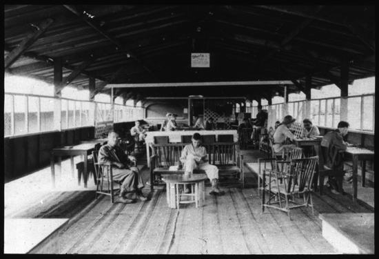 Interior view of Red Cross recreation hall. Desks and chairs occupied with men.