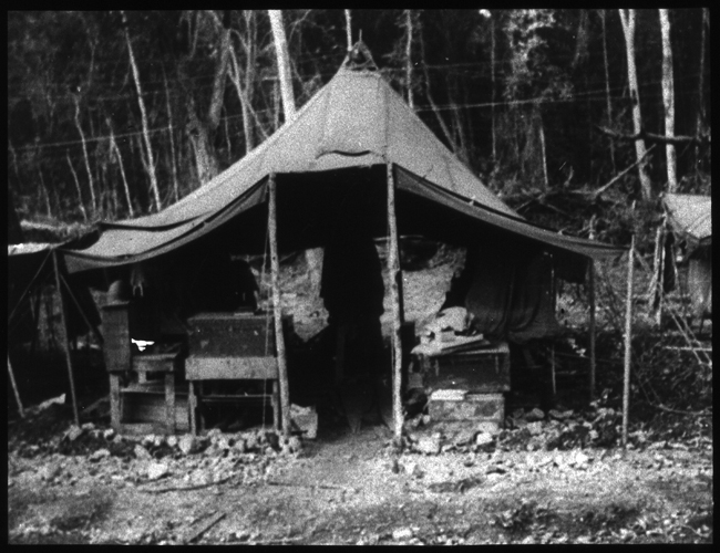 Exterior shot of an open tent as part of a row of tents, with various storage and chests underneath.